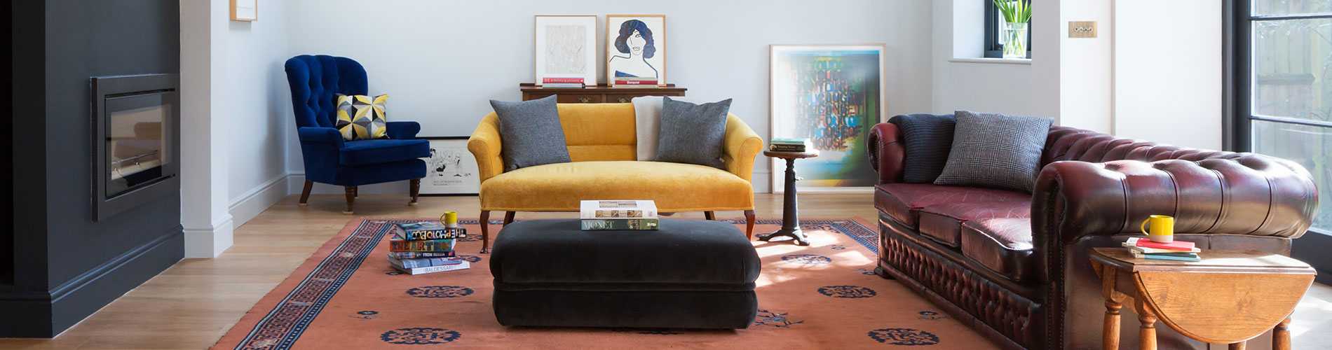 open plan living room library with dividing fireplace and oak floor vintage Chesterfield and coloured velvet seating
