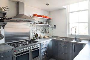 kitchen refurbishment East London interior design with open shelving Le Creuset pans and stainless steel worktop