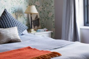 cosy guest bedroom with sea green Zoffany Romey Garden wallpaper on walls and Farrow & Ball Peignoir eggshell on woodwork