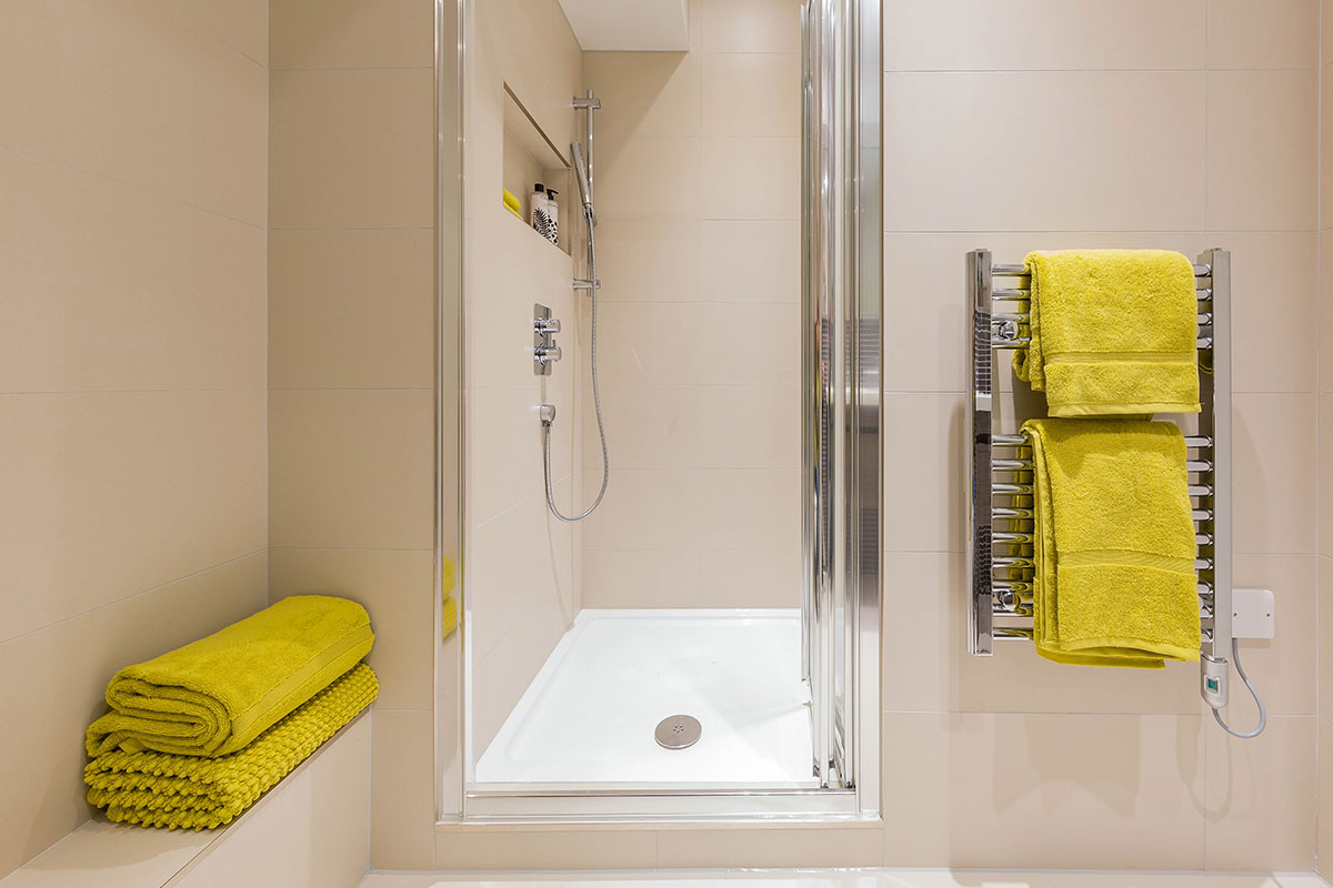 Verve Properties West London flat relaxing shower room with neutral wall tiles and bright yellow towels from John Lewis