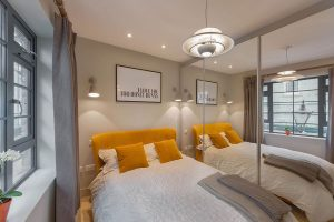 interior design of bedroom for Brenford flat by Element Studios with mirrored wardrobes and Smoke burnt orange bed from Loaf