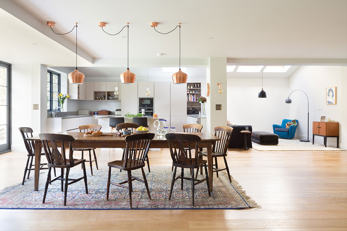 open-plan ground floor dining room and German kitchen with draped Heals copper Cohen pendants and reclaimed table and chairs