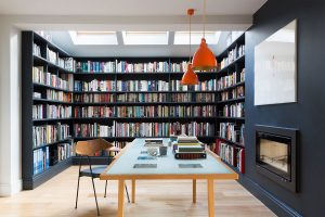 central fireplace dividing bespoke library with mid-century desk and chair orange Jielde pendants from Holloways of Ludlow