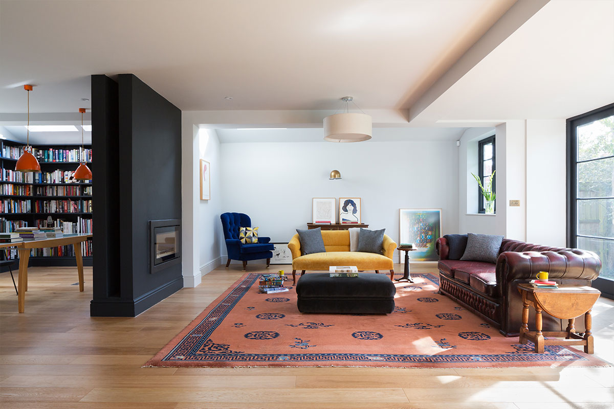 open-plan living room and library with dividing fireplace and oak floor vintage Chesterfield and coloured velvet seating