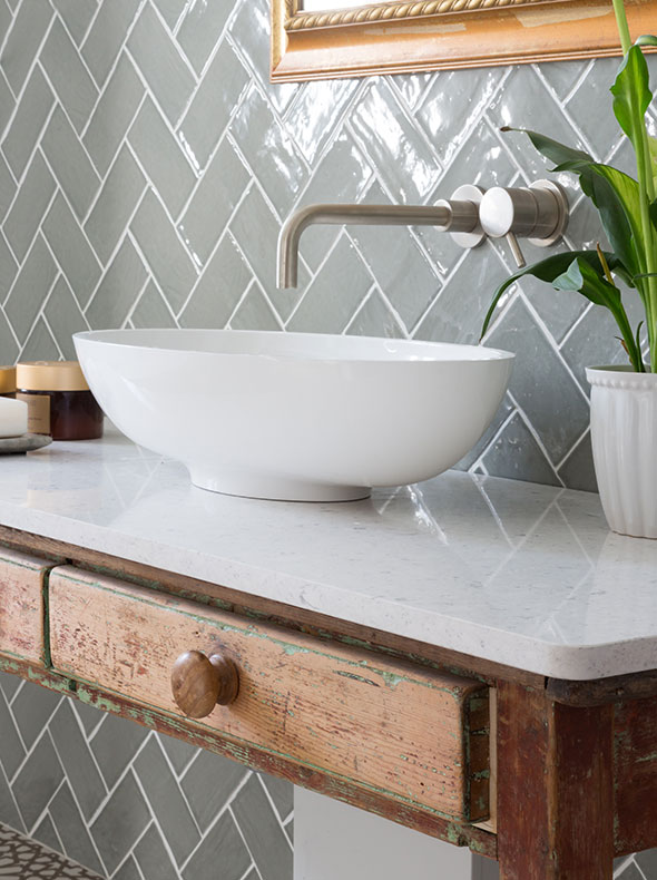 wall mounted brushed steel taps over stone basin and worktop with vintage desk as wash stand from Oxford interior designers