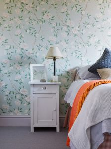 vintage bedside table in guest bedroom with Zoffany Romey's Garden wallpaper on walls and Peignoir eggshell on woodwork
