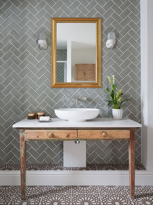 eclectic design of bathroom with sage herringbone tiles and Thomas Hoof porcelain wall lights from SCP behind reclaimed desk