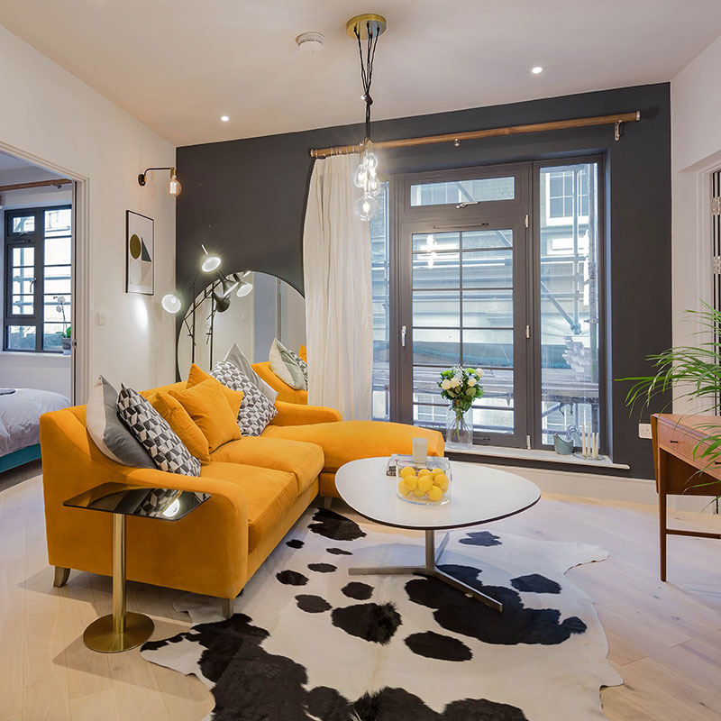 Brentford flat interior by Element Studios with Loaf Oscar burnt orange sofa, cowhide rug and Tom Dixon Flash side table