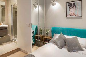 Verve Properties Brentford flat designed by Element Studios with retro bedside tables and Belize velvet blue bed from Loaf