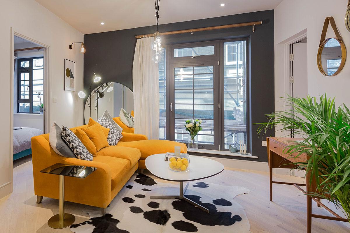 Brentford flat Tom Dixon Flash side table cowhide rug Oscar velvet burnt orange sofa Junction wall lights Tom Pigeon prints