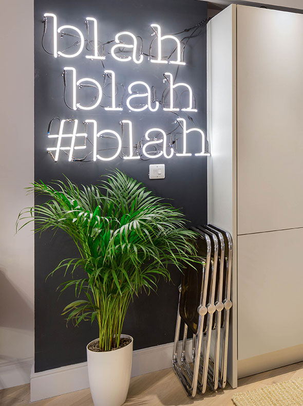 Farrow and Ball Railings painted wall with neon blah blah blah sign with green plant and Pamono vintage Castelli folding chairs
