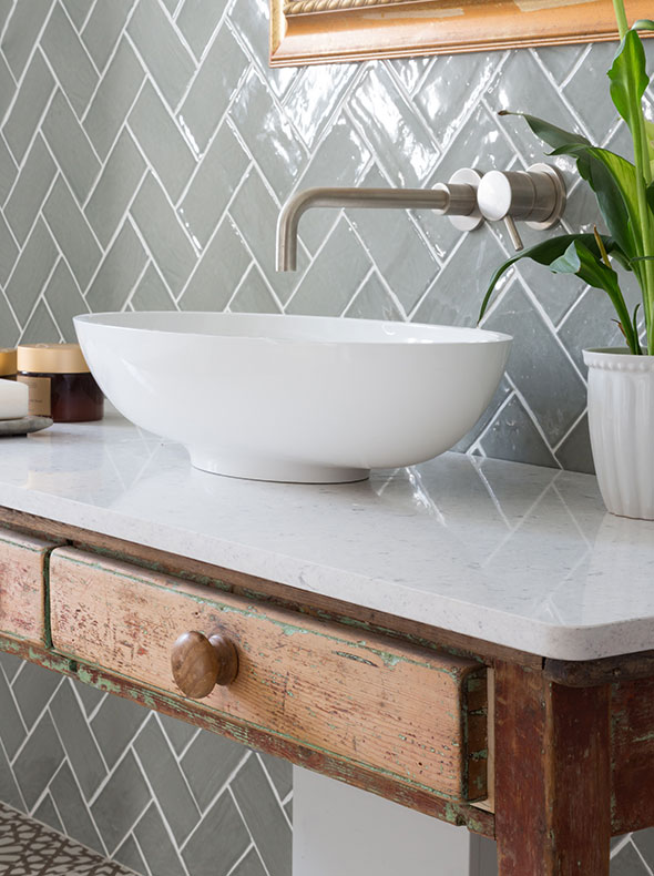bathroom design by Element Studios showing close-up of vintage wash stand with stone worktop and sage herringbone wall tiles