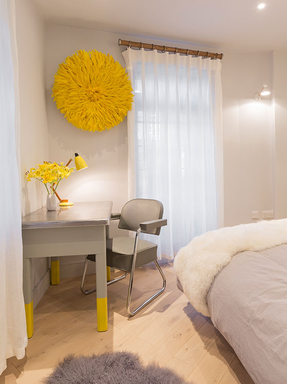 contemporary bedroom interior showing 1950s French writing desk with grey tub chair and Juju yellow hat on wall behind