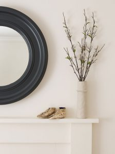 close-up of circular mirror in Railings and fireplace in School House White, Farrow & Ball paints with small ceramic vase