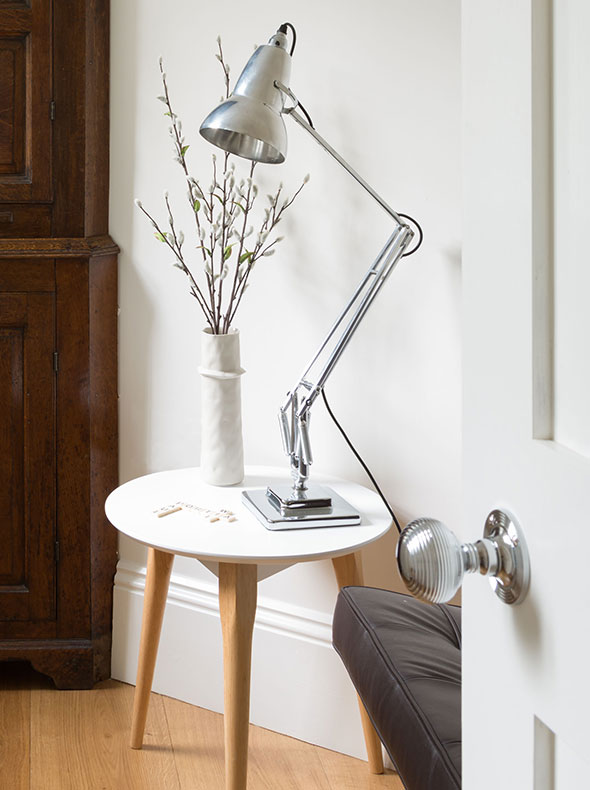 refurbished entrance hall listed building with chrome Anglepoise lamp antique cupboard and Mies van der Rohe Barcelona Chair