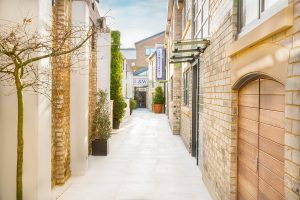 stone paved mews walkway to Loud and Western townhouse redevelopment with private entrances to houses in Fulham during autumn